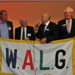 Flag Ceremony Tony Broadhurst presenting the flag to Jan Johansson who will act as World President for the 22nd WALG Tournament in Belek Turkey. Also present Doug Crosby (WALG Chairman) and Peter Read WALG Secretary.